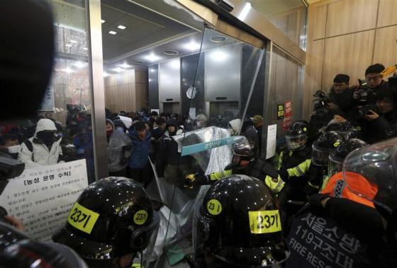 Policemen break down the glass door at the Korean Confederation of Trade Union head office during a protest by members of KCTU in Seoul