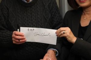 촘스키 교수가 서명을 마친 $47이 든 봉투를 건네주고 있다.