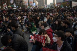 Anti-government protesters hold placards as they sit on a street in central Seoul on November 12, 2016. Up to one million people were expected to take to the streets of Seoul to demand the resignation of scandal-hit President Park Geun-Hye, in one of the largest anti-government protests in decades. / AFP PHOTO / Ed JONESED JONES/AFP/Getty Images