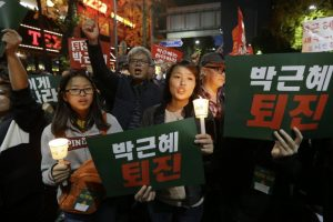 "Protesters shout slogans as they march toward presidential house after a rally calling for South Korean President Park Geun-hye to step down in Seoul, South Korea, Saturday, Nov. 12, 2016. Hundreds of thousands of people flooded Seoul's streets on Saturday demanding the resignation of Park amid an explosive political scandal, in what may be South Korea's largest protest since it shook off dictatorship three decades ago. The letters read ""Park Geun-hye should step down."" (AP Photo/Ahn Young-joon)"