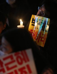 epa05627942 A protester holds up a candle during a rally in the city of Jeju on South Korea's largest island of the same name on 12 November 2016, to call for President Park Geun-hye's resignation over an influence-peddling scandal implicating her longtime close friend Choi Soon-sil. EPA/STRINGER SOUTH KOREA OUT